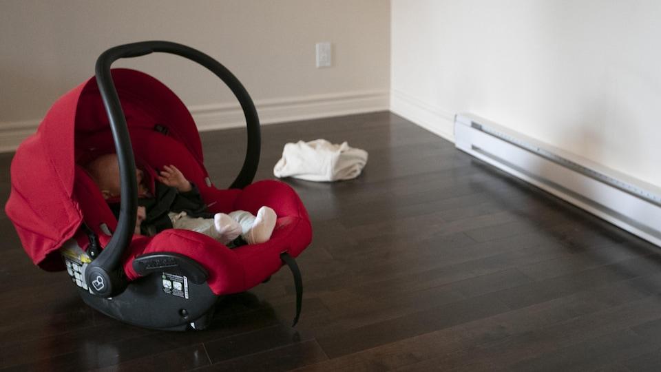 Un bébé vu de profil pleure dans son fauteuil posé sur le sol d'un logement vide.
