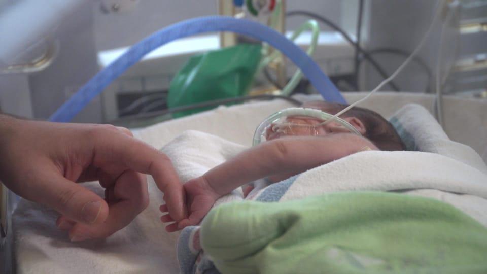 Un bébé entubé dans une couveuse tenant la main d'un adulte