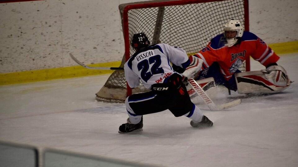 Un joueur tente de marquer un but. Le gardien se déplace vers lui.