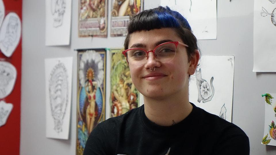 Une jeune femme au nez percé, aux cheveux noirs relevés avec des mèches bleues pose devant un mur couvert de dessins. Elle porte un t-shirt noir qui laisse entrevoir un tatouage naissant au bas du cou.