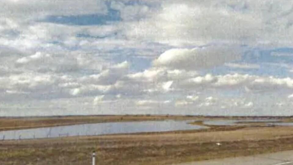 Un plan d'eau se situe dans un champ près d'une route