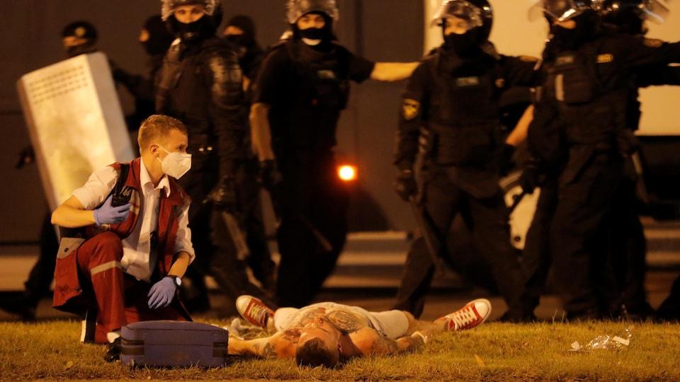 Un secouriste est agenouillé près d'un homme étendu au sol.