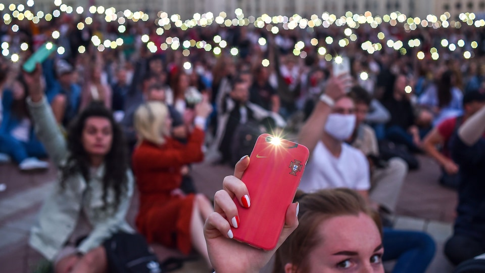 Des centaines de manifestants tiennent leur téléphone intelligent en l'air, lampe allumée.