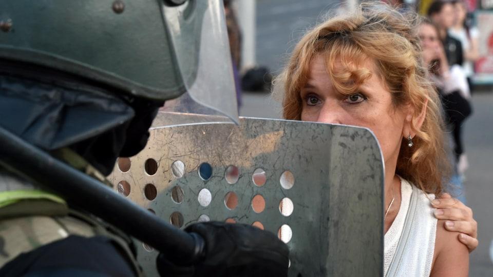 Une femme regarde un policier lourdement armé.