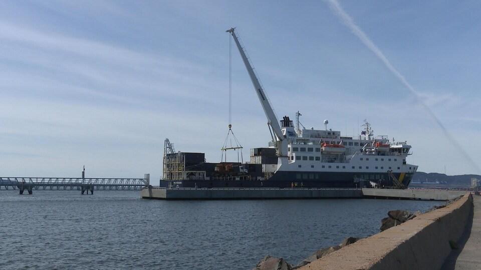 La grue déplace un camion vers l'intérieur du bateau.