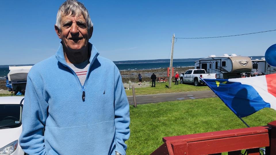 Russell Comeau debout près de sa roulotte devant la mer.