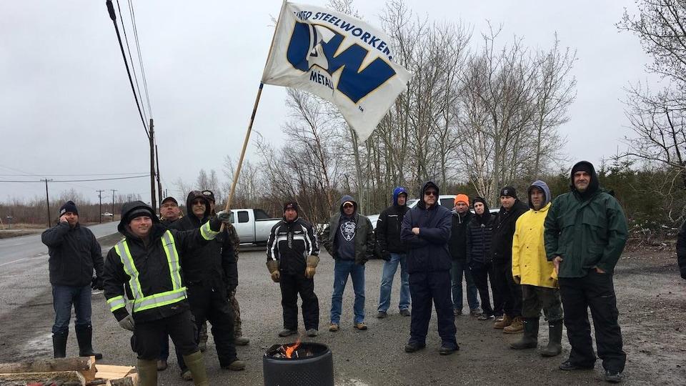 Une dizaine de travailleurs rassemblés autour d'un feu de camp. L'un d'eux brandit un drapeau syndical.