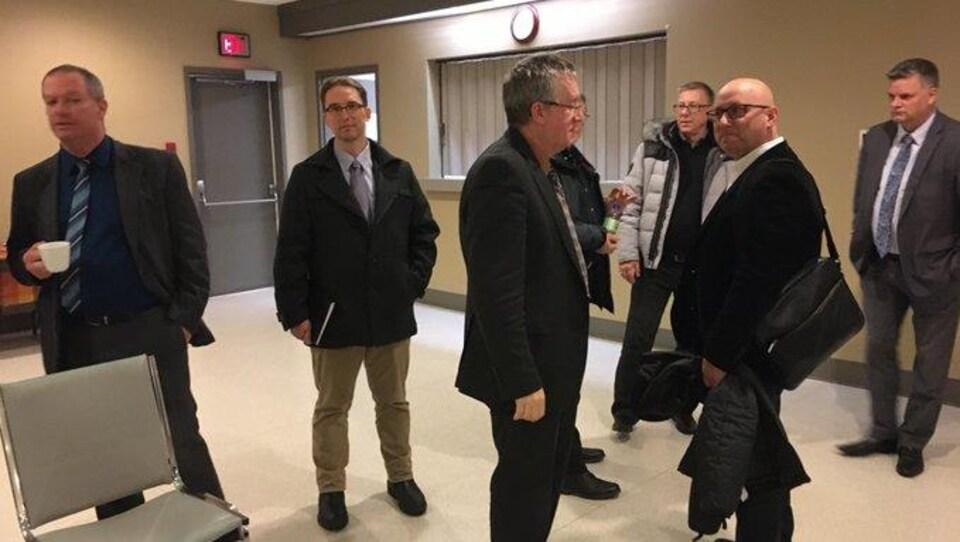 Sept hommes debout dans une petite salle de réunion