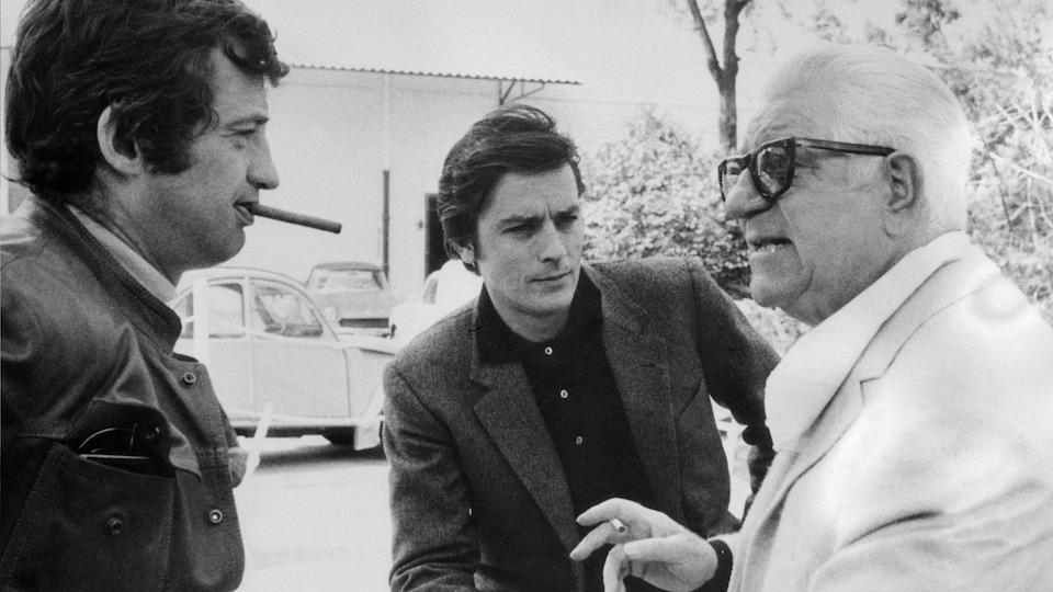 Les trois hommes discutent ensemble. Jean-Paul Belmondo fume une cigarette.