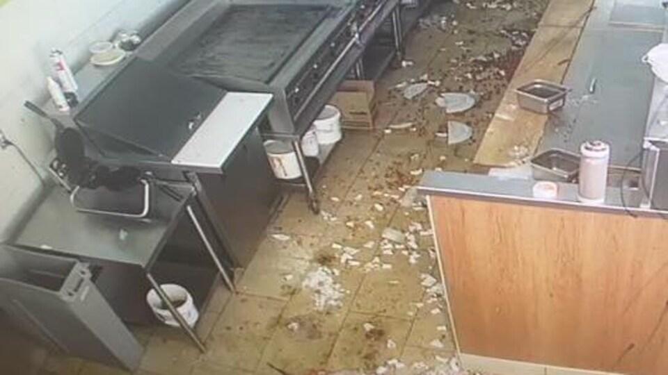 De la vaisselle brisée et de la nourriture éparpillée au sol dans les cuisines d'un restaurant.