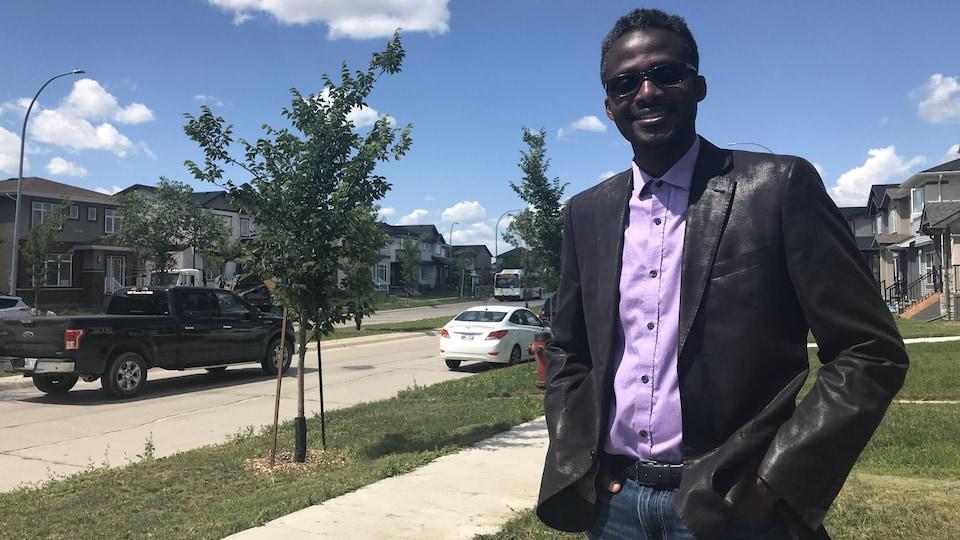 Un homme noir en veste debout à l'extérieur.