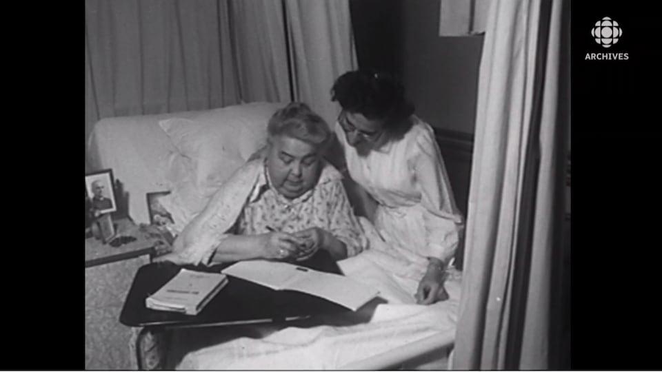 Une femme dans son lit qui écrit dans un cahier et, à côté d'elle, une autre femme qui la regarde.