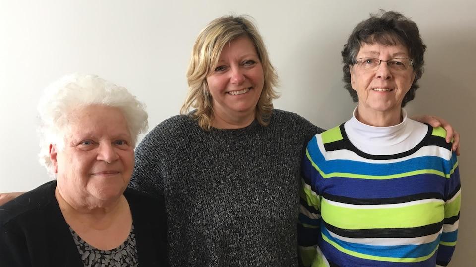 Trois femmes posent pour la caméra.