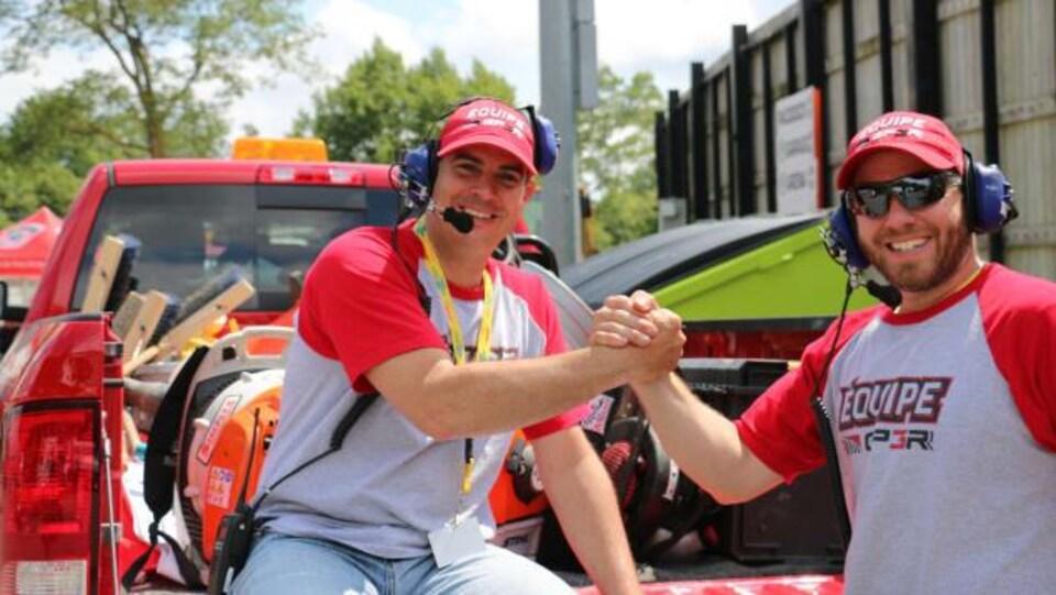 Deux hommes se serrent la main en souriant. Ils portent des chandails de l'équipe de bénévoles du Grand Prix de Trois-Rivières.