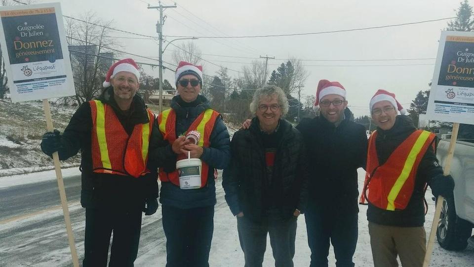 Cinq bénévoles tout sourire avec des dossards sur le bord de la route.
