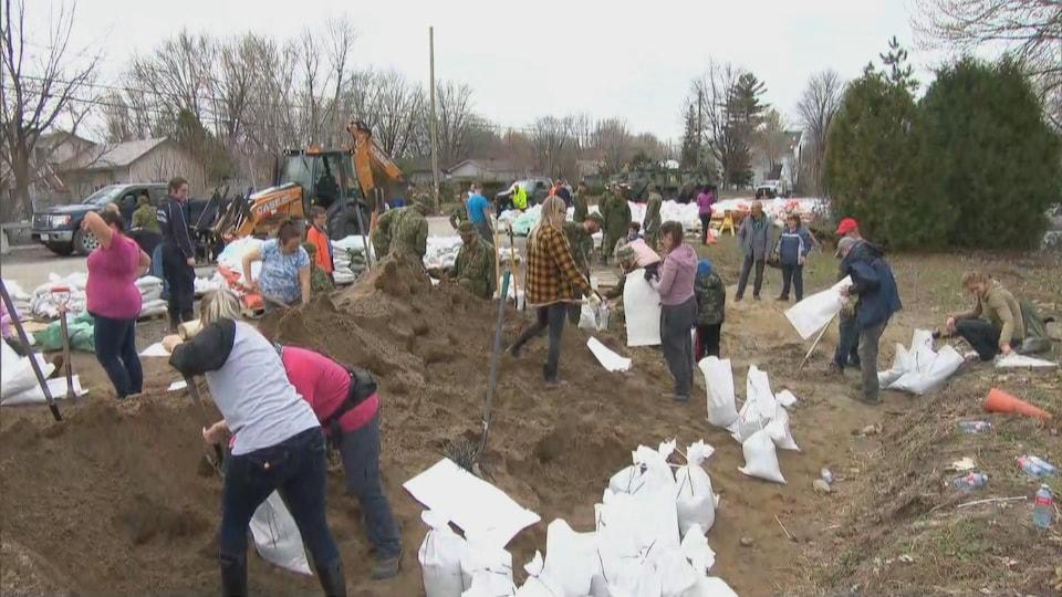 Des bénévoles remplissent des sacs de sables à Gatineau.