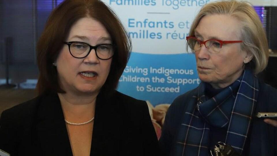 Deux femmes avec des lunettes répondent aux questions des journalistes.