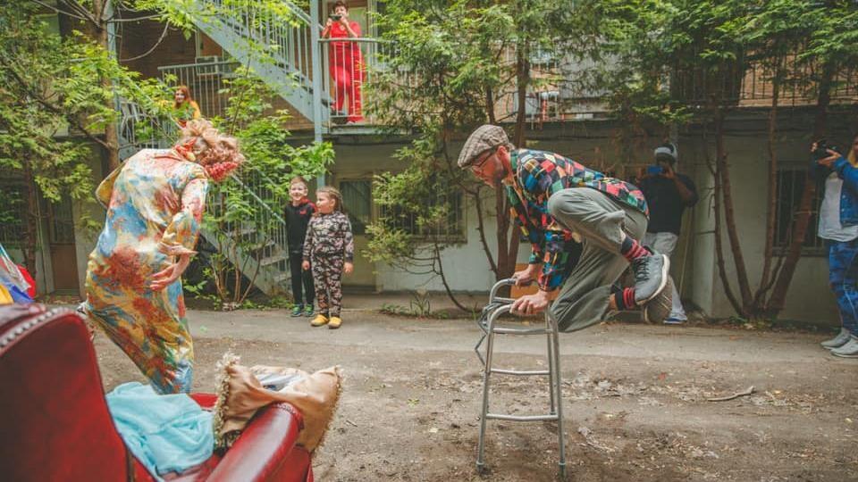 Un clown fait un saut dans les airs en appuyant ses mains sur une marchette.