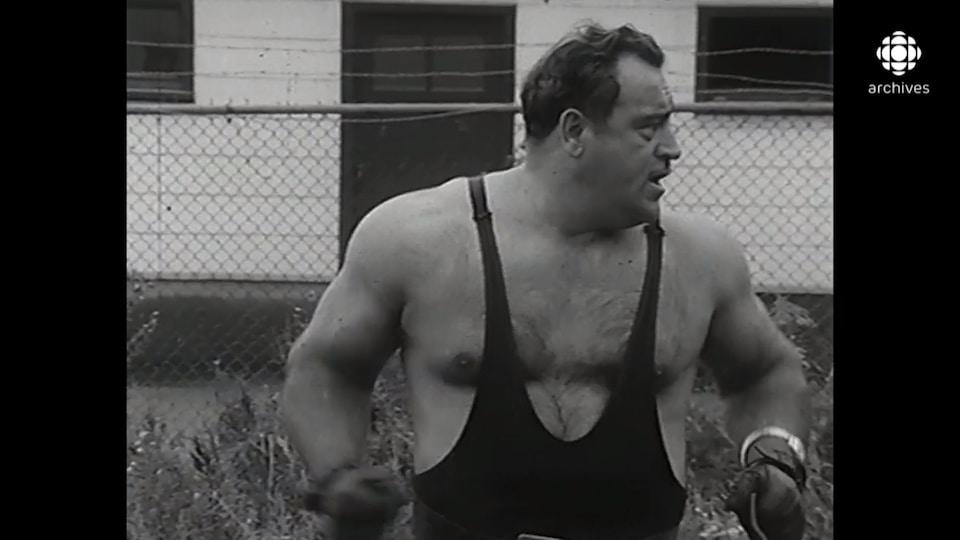 Benoît Côté porte un maillot de lutteur et semble forcer.