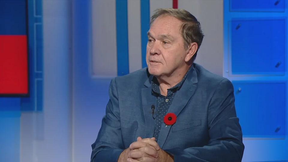 Gilles Benoit interviewé dans un studio de télévision.