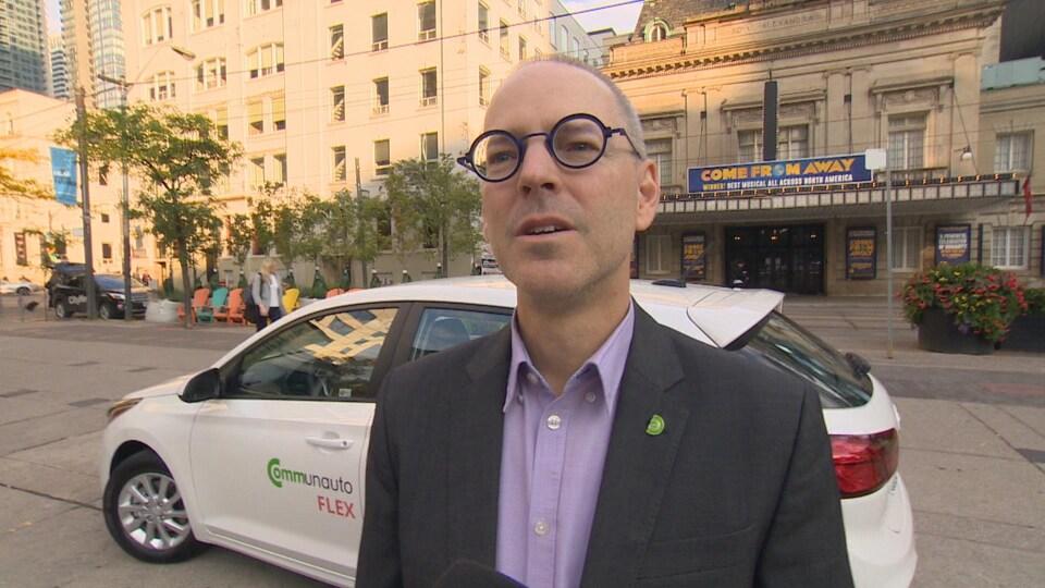 Le président et fondateur de Communauto Benoît Robert porte des lunettes rondes et violettes, un veston gris et une chemise violet clair, il parle au micro de Radio-Canada il est dehors, devant une voiture Communauto