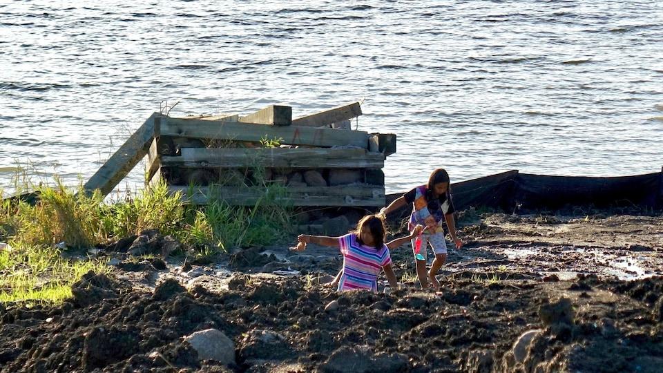 Deux jeunes Ojibwées marchent dans la boue sur les berges de la rivière English, dans la réserve de Grassy Narrows