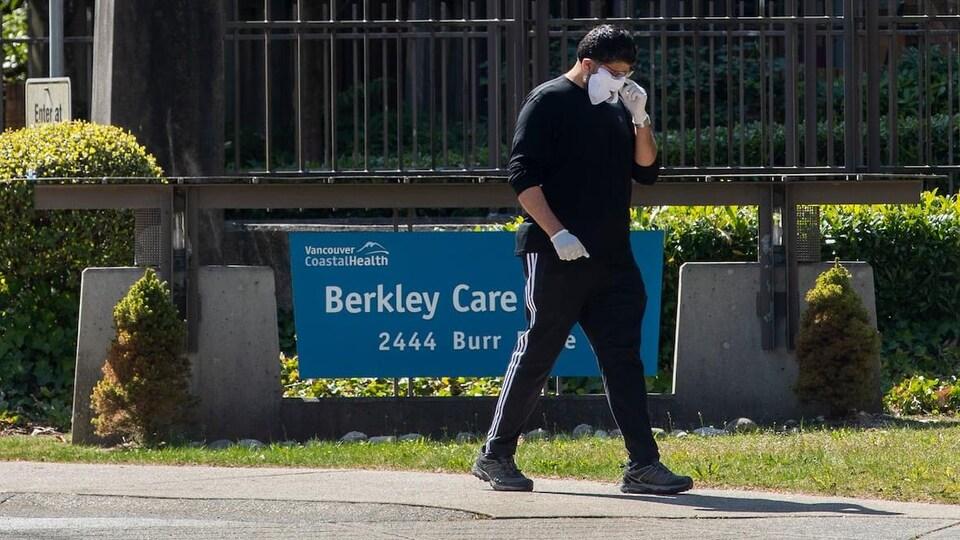 Un homme porte un masque et marche à l'extérieur du centre de soins Berkley à North Vancouver.