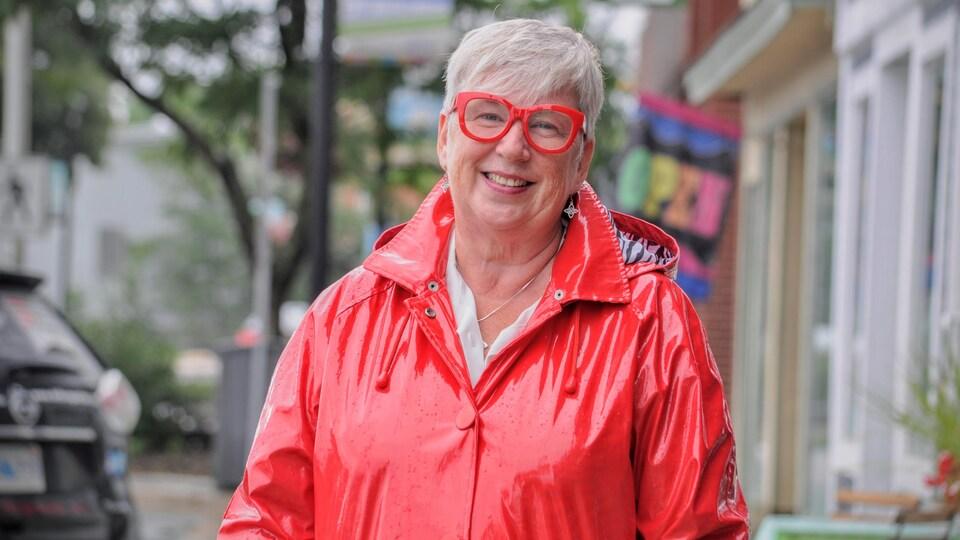 Un femme dans un imperméable rouge sourit pour la caméra.