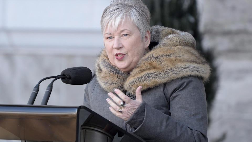 Bernadette Jordan à l'extérieur devant un micro, vêtue d'un manteau d'hiver.