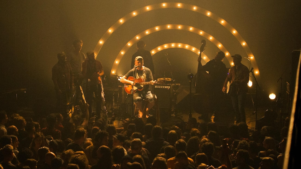 Le public au parterre regarde le chanteur sur scène, entouré d'autres musiciens.