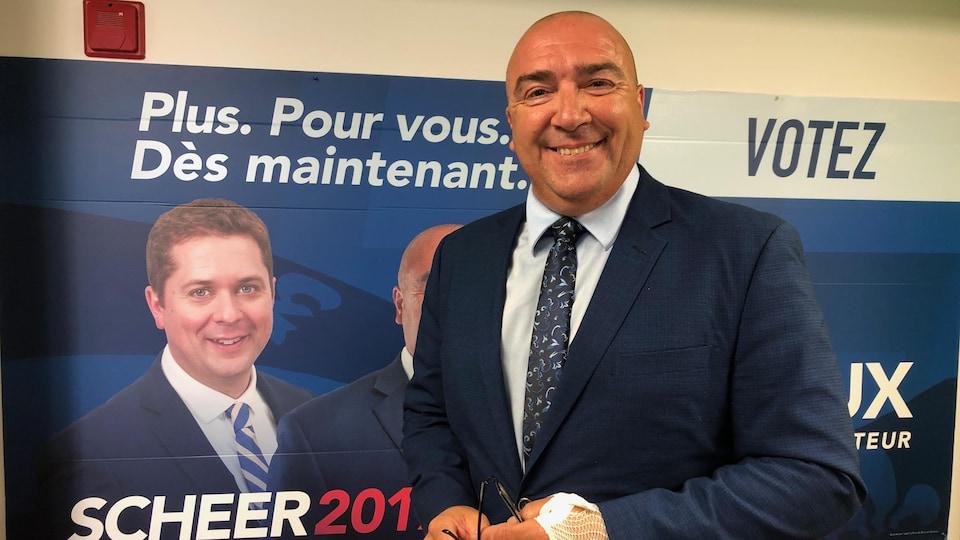 Bernard Généreux devant une pancarte électorale