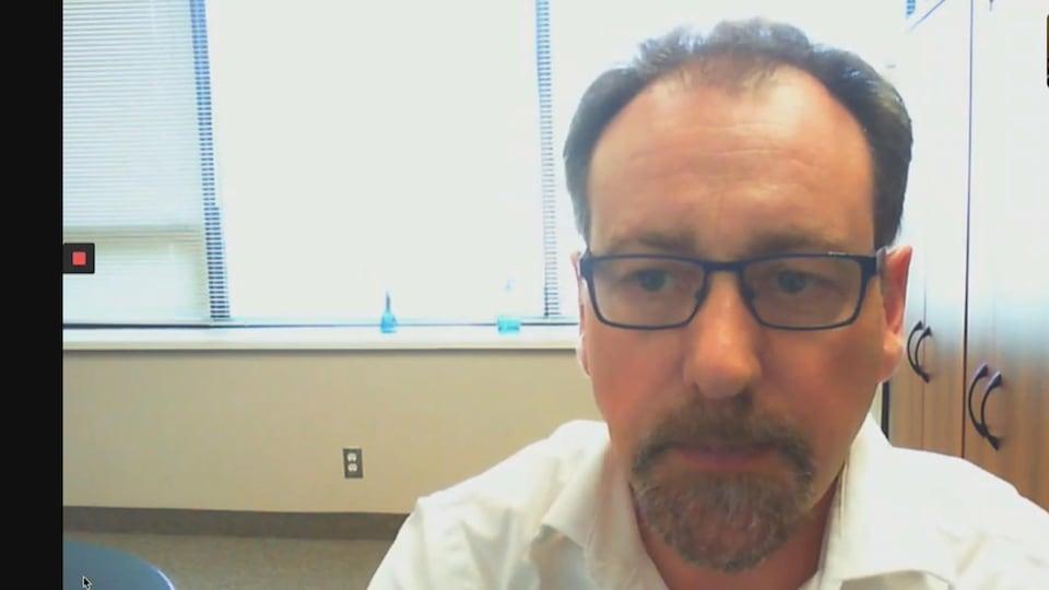 Dr Bernard Le Foll, Centre de toxicomanie et de santé mentale à Toronto en entrevue Skype - il a les cheveux bruns, porte des lunettes, les yeux bleus, une barbichette poivre et sel et une chemise blanche.