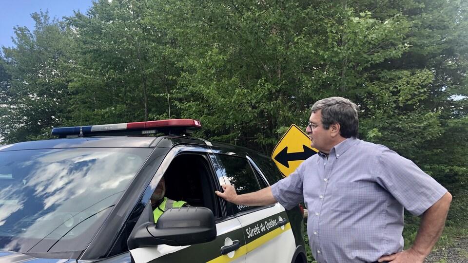 Le maire de la municipalité, Bernard Ouellet, discute avec un policier.