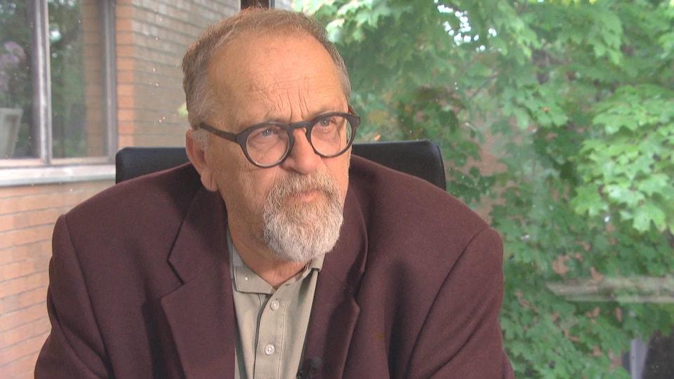 Bernard Thériault assis dans un bureau devant une grande fenêtre.