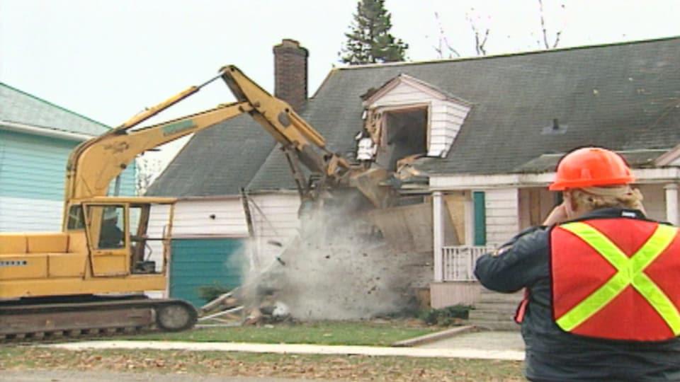 Une pelle mécanique qui détruit une petite maison