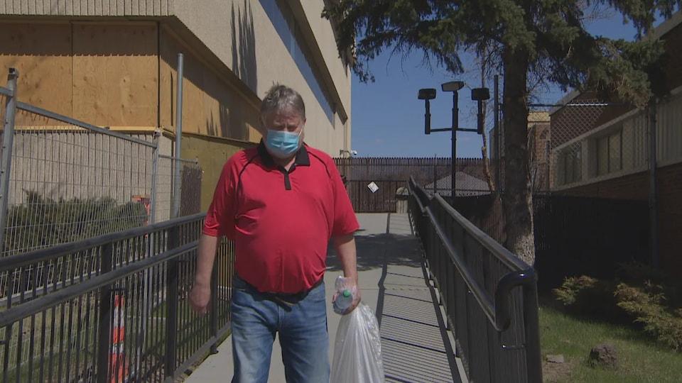 Un homme tient un sac et une bouteille dans la main et porte un masque.
