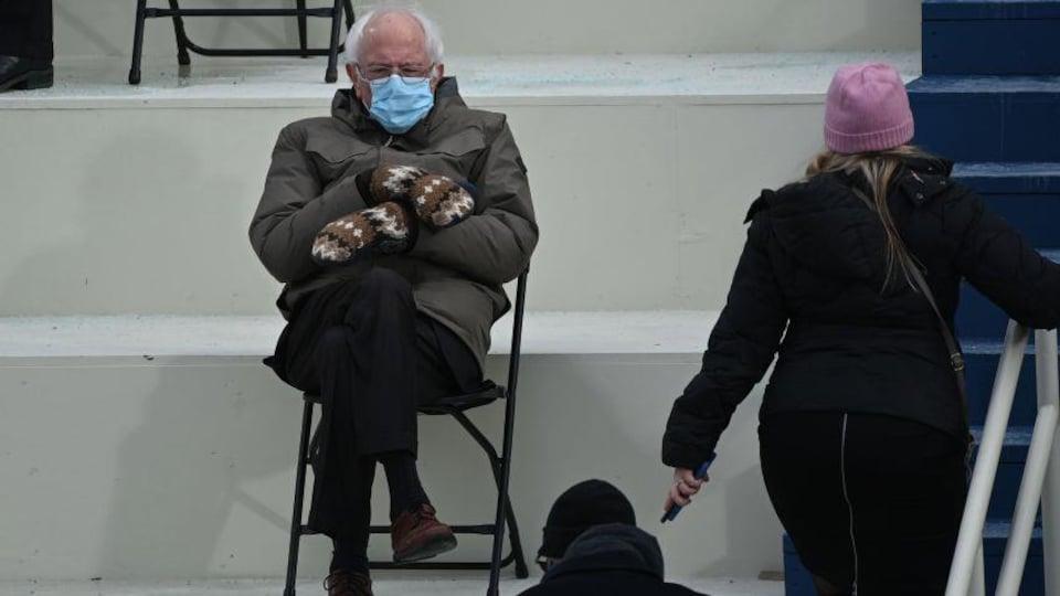 Un vieil homme habillé chaudement, assis sur une chaise pliable portant un masque.