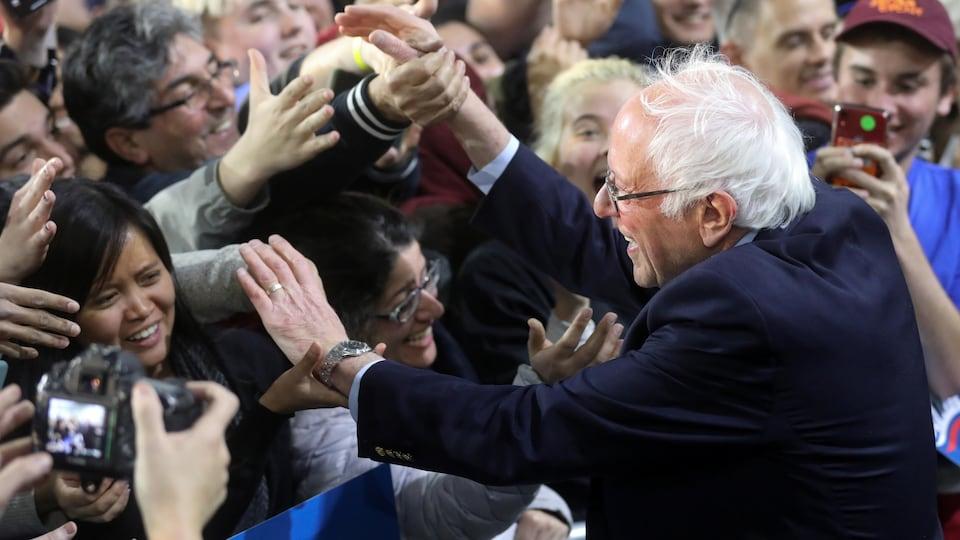 Bernie Sanders serre la main de militants dans une foule.