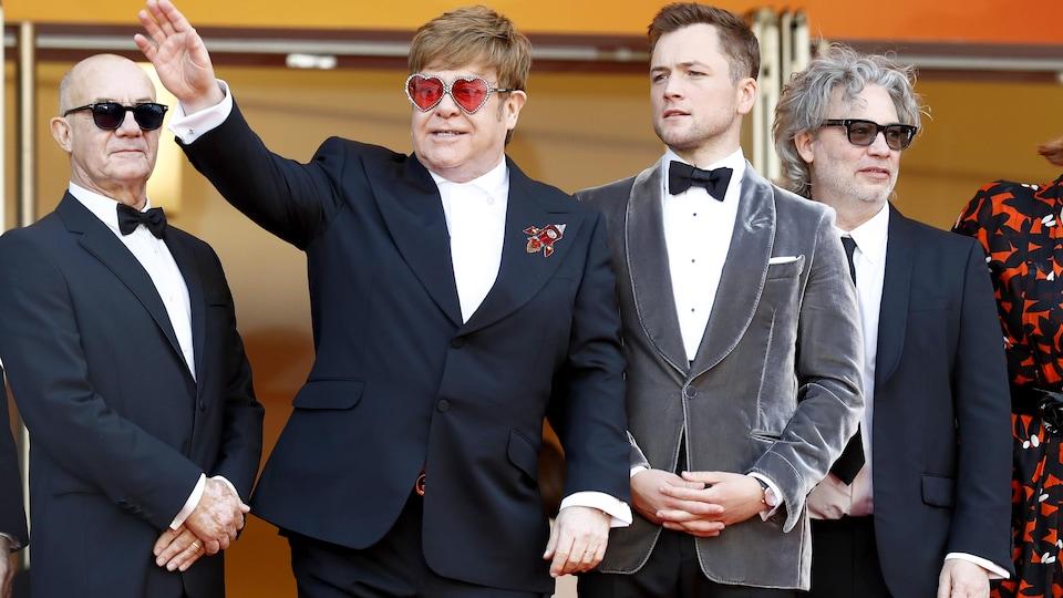 L'un des hommes, Elton John, salue les gens de la main.