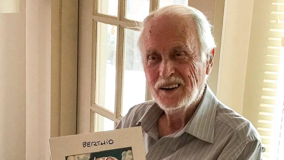 Un homme à la barbe blanche tient un album entre ses mains.