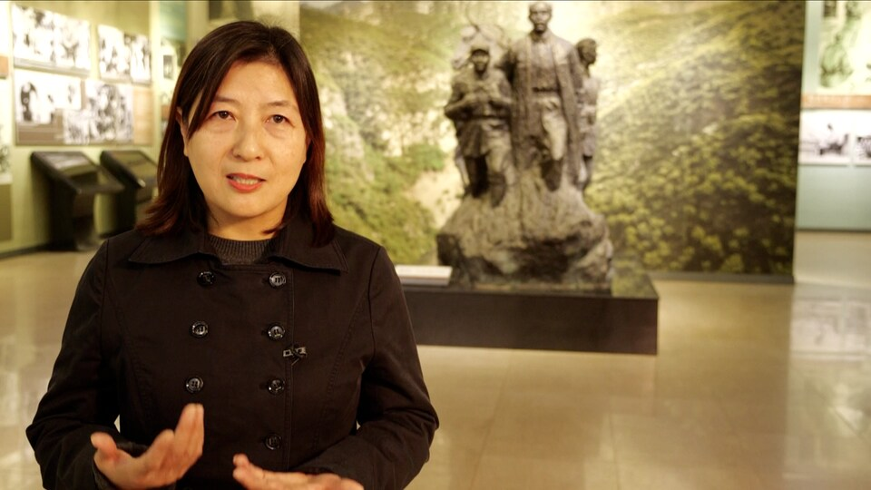 Une femme est debout et parle devant l'une des statues représentant le médecin canadien Norman Bethune.