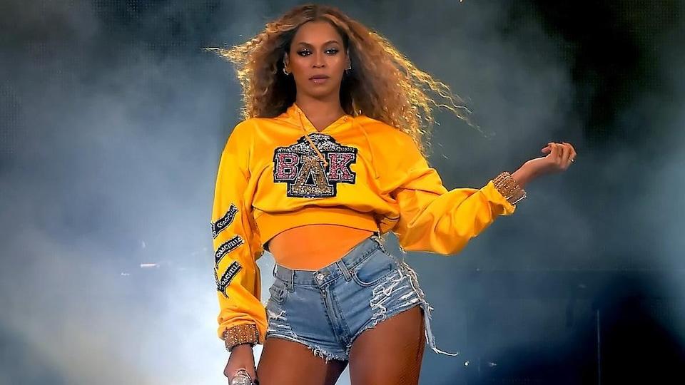 Beyonce porte un chandail jaune et un court short en jean.