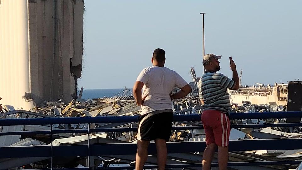 Des gens observent les débris.