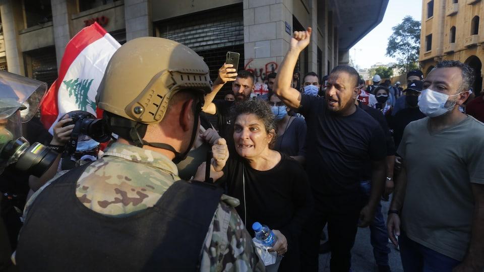 Un soldat libanais fait face à une femme en colère et à des dizaines de manifestants derrière elle.