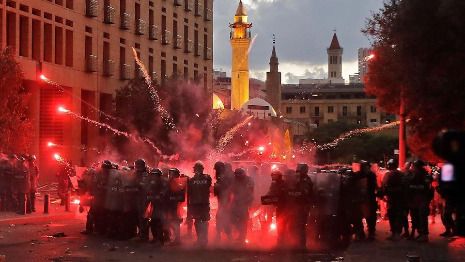 Des policiers en tenue anti-émeute sont bombardés de feux d'artifice.