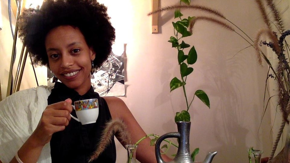 Une jeune femme tient une tasse.