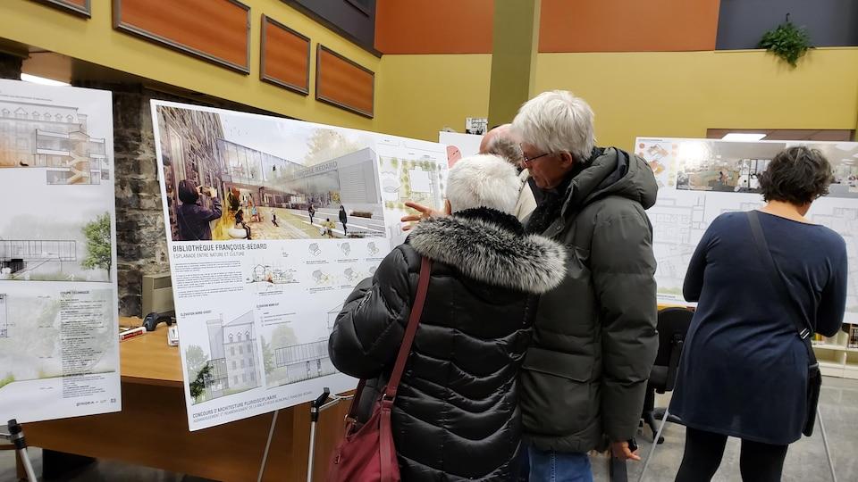 Deux personnes observent les esquissent de la future bibliothèque de Rivière-du-Loup.