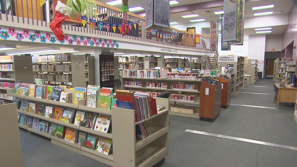 Plusieurs livres reposent sur les rayons d'une bibliothèque.