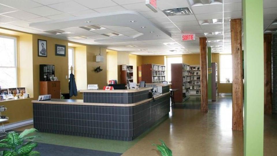 Le comptoir au centre de la salle est revêtu de tuiles noires et entouré de casiers de livres.
