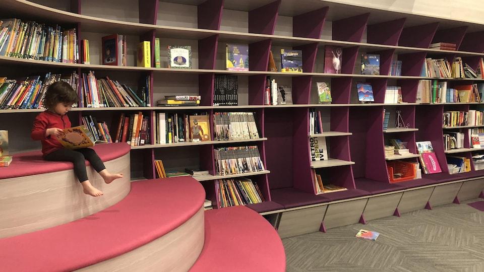 Une fillette de trois ans qui lit un livre sur un banc de la bibliothèque.